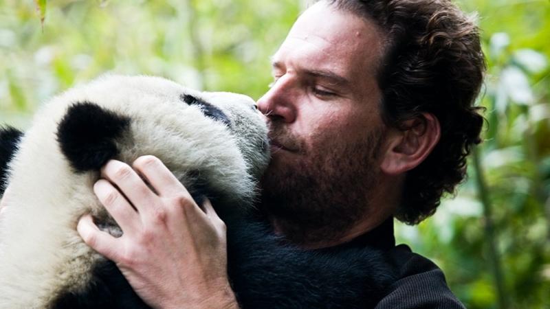 Charlie Annenberg hugs a panda at Wolong Preserve